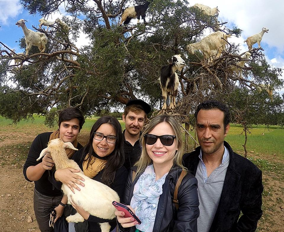 Nós e nosso guia em frente a uma árvore cheia de cabras.