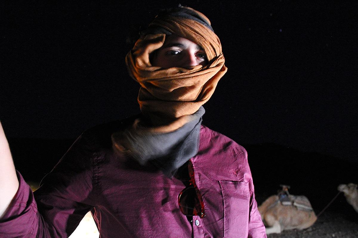 Rodrigo de turbante na entrada do deserto de Zagora a noite com camelos ao fundo.