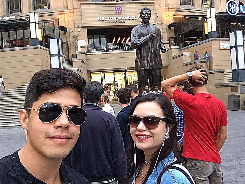 O Rodrigo e eu em frente a estátua do Nelson Mandela no shopping Nelson Mandela Square em Joanesburgo.