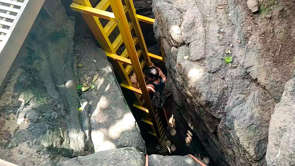 Rodrigo descendo uma escada amarela entre as rochas que leva até a praia do Sancho.