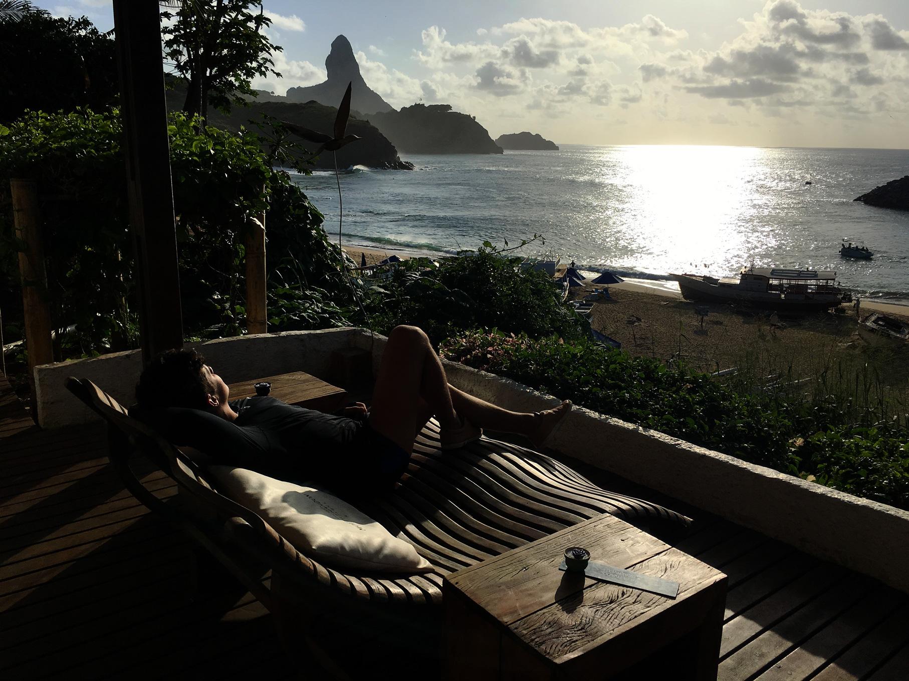 Rodrigo sentado em uma espreguiçadeira de frente para o mar no Bar mergulhão em Ferndando de Noronha.
