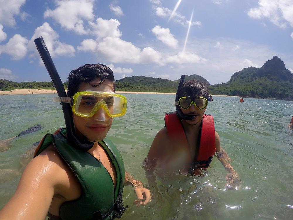 Rodrigo e Henrique no mar vestindo colete e snorkel.