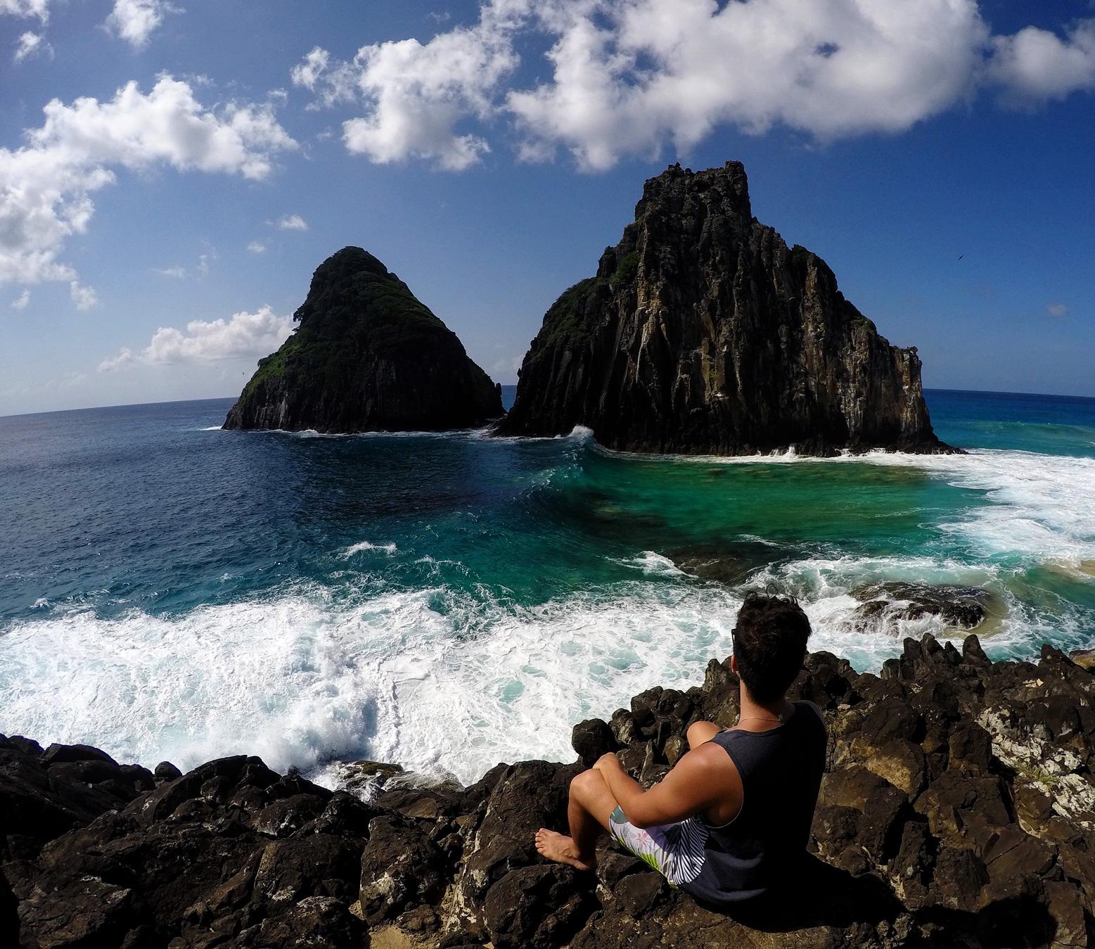 Rodrigo sentado nas rochas admirando o morro Dois Irmãos.