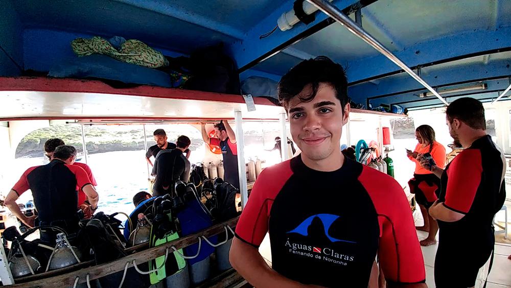 Rodrigo no barco com a roupa de mergulho da empresa Águas Claras.