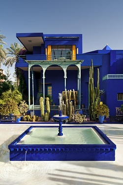 Palmeiras e fonte azul do Jardin Majorelle em Marrakech, Marrocos
