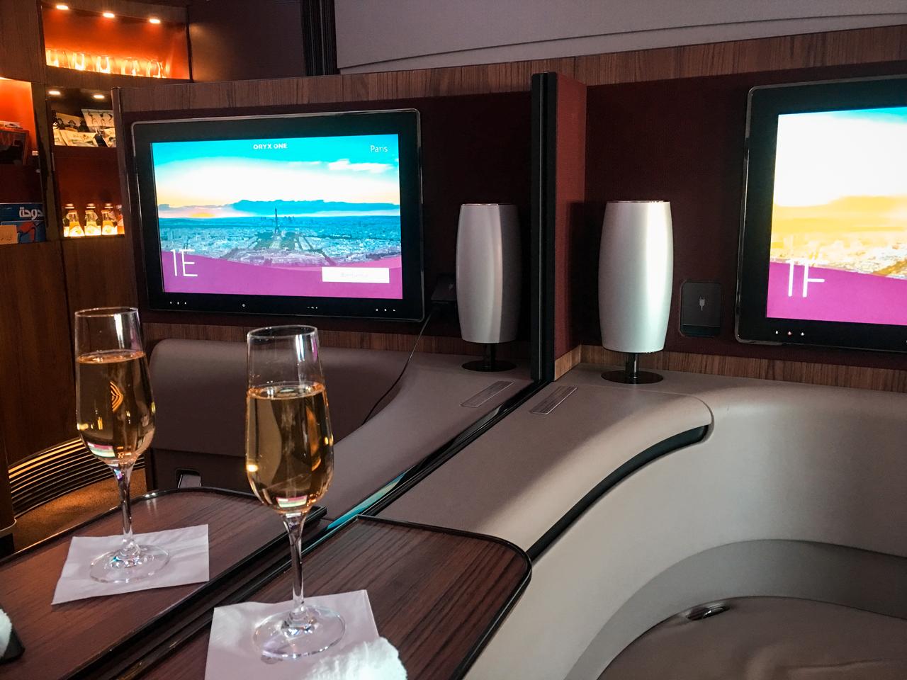 Nossa cabine da primeira classe Qatar Airways. Caso você esteja viajando sozinho, a divisória do meio sobe para maior privacidade