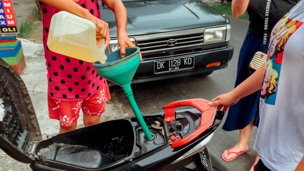 Mulher abastecendo uma scooter com um galão de gasolina.